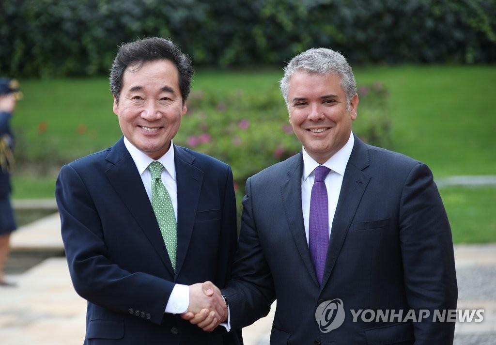 当地时间5月6日,在哥伦比亚波哥大总统府,韩国国务总理李洛渊(左)和哥伦比亚总统伊万·杜克握手合影。(韩联社)