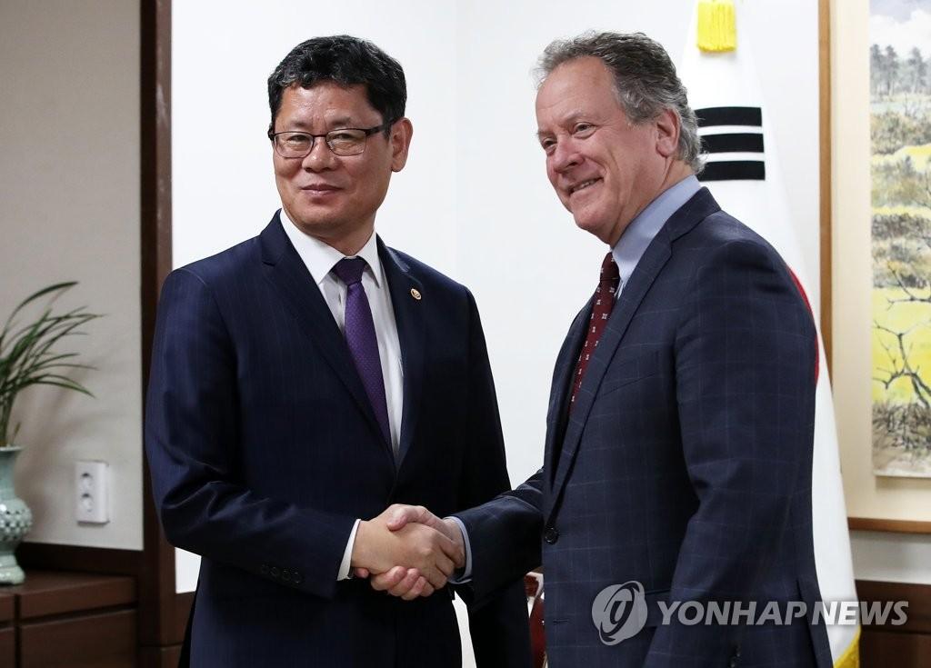 金炼铁(左)和比斯利亲切握手。(韩联社)