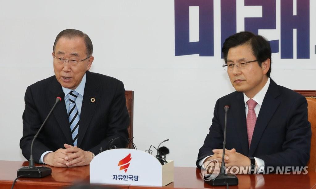 5月17日,在国会,潘基文(左)与黄教安进行交谈。(韩联社)