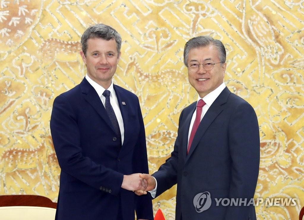 5月20日上午,在青瓦台,文在寅(右)和弗雷德里克握手。(韩联社)