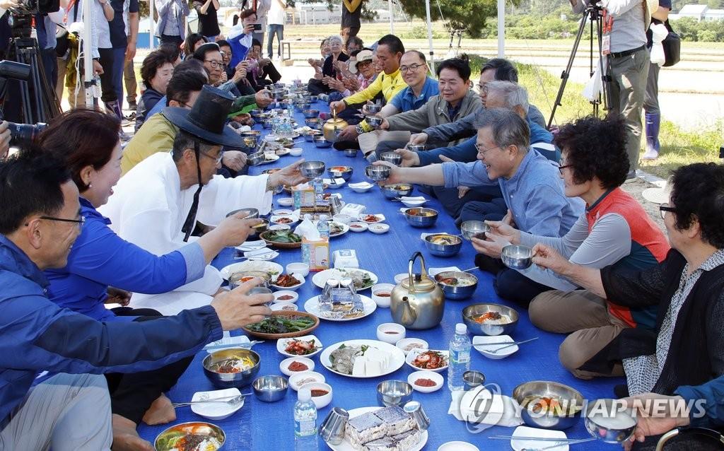 5月24日上午,在庆尚北道庆州市安康邑玉山村,文在寅(右三)插秧后与居民们就餐。(韩联社)