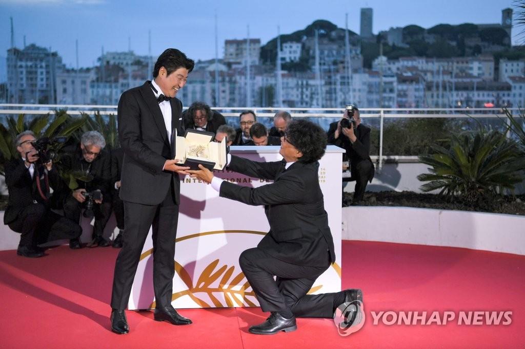 名导奉俊昊(右)单膝跪地将奖杯献给演员宋康昊(韩联社)