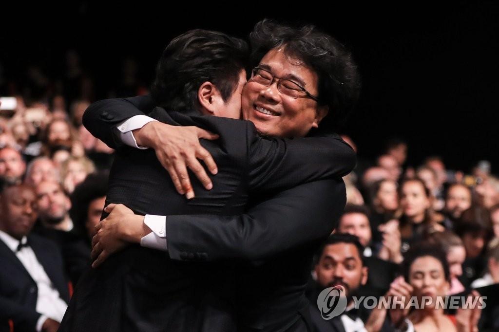 当地时间5月25日,在法国戛纳,韩国名导奉俊昊凭借《寄生虫》在第72届戛纳电影节上获颁最高奖项——金棕榈奖。图为奉俊昊(右)和主演宋康昊在得知获奖后相拥庆祝。(韩联社/欧新社)