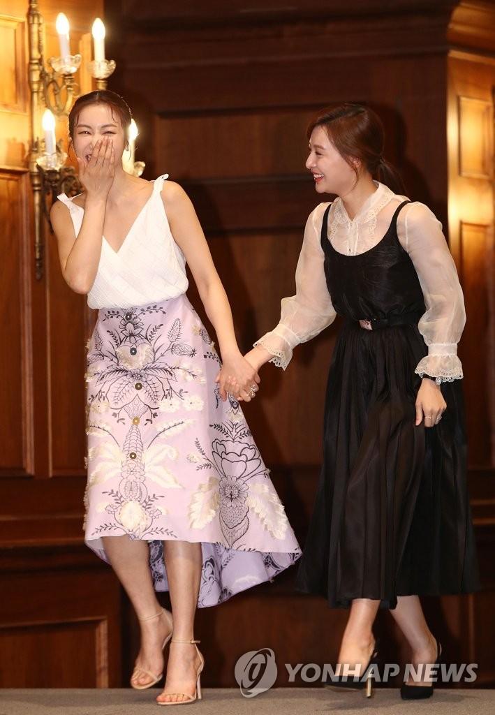 5月28日,在首尔皇宫酒店,演员金智媛(右)与金玉彬手牵手出席新剧《阿斯达年代记》发布会。(韩联社)