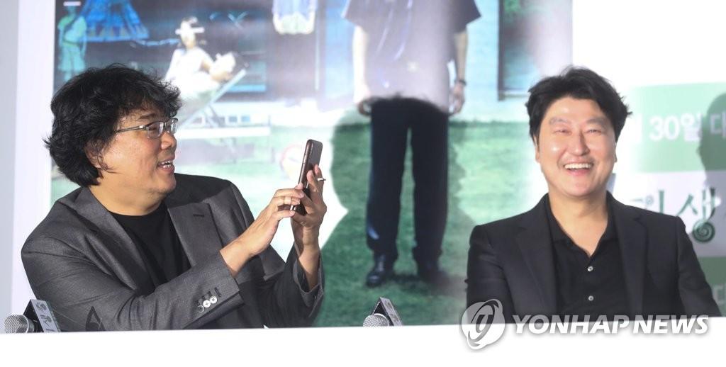 奉俊昊(左)和宋康昊出席《寄生虫》试映会。(韩联社)