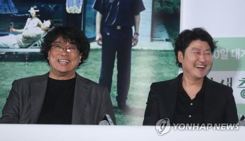5月28日下午,在首尔市龙山区汉江路洞CGV影城龙山爱宝客店,奉俊昊(左)和宋康昊在《寄生虫》记者座谈会上开怀大笑。(韩联社)