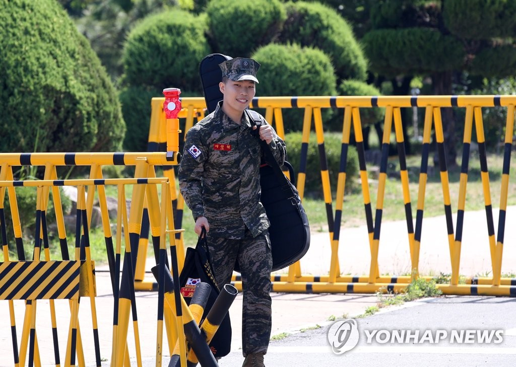 5月29日,在庆尚北道南区乌川邑海军陆战队第一师,李赞赫拎着包扛着吉他离开部队。(韩联社)
