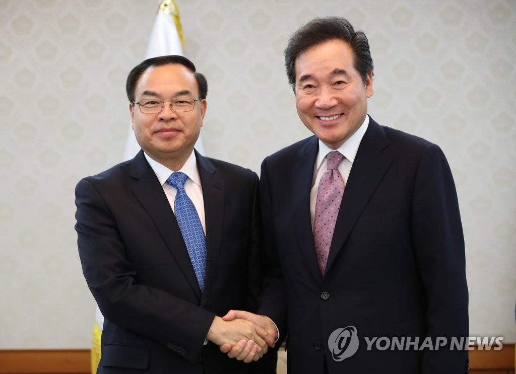 5月30日,在政府首尔大楼,李洛渊(右)与重庆市长唐良智握手合影。(韩联社)