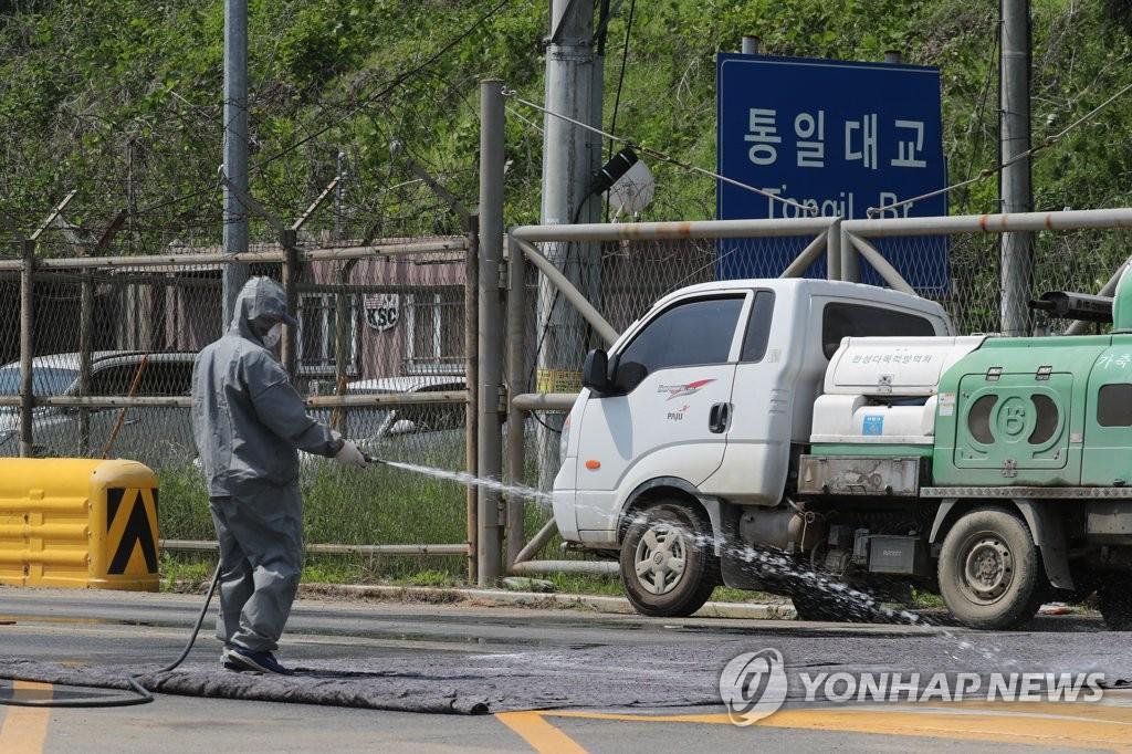 资料图片:6月3日,在京畿道坡州市统一大桥北侧限行地区,有关部门正在对道路喷洒消毒药品。(韩联社)
