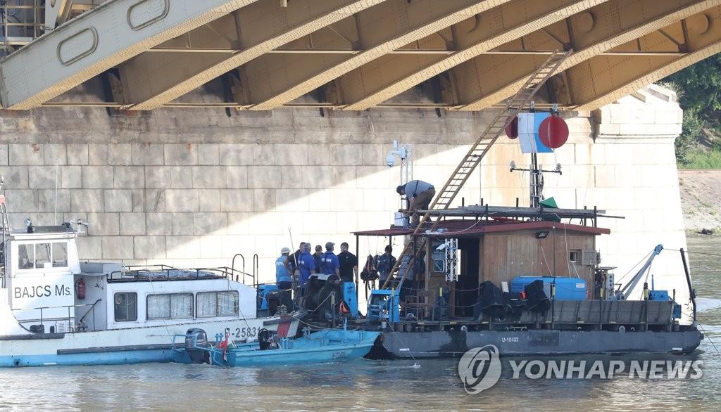 当地时间6月5日,在布达佩斯多瑙河上,沉船事故搜救队的有关人士在交谈。(韩联社)