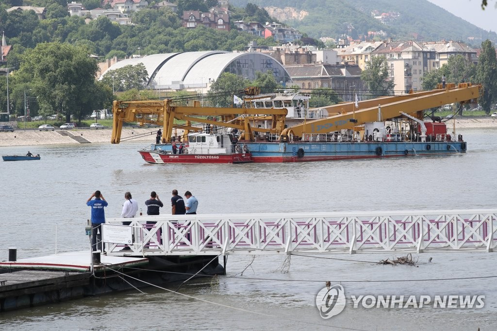 资料图片:当地时间6月7日,在匈牙利沉船事发地附近,一艘起重船驶向多瑙河上的玛尔吉特桥。 韩联社