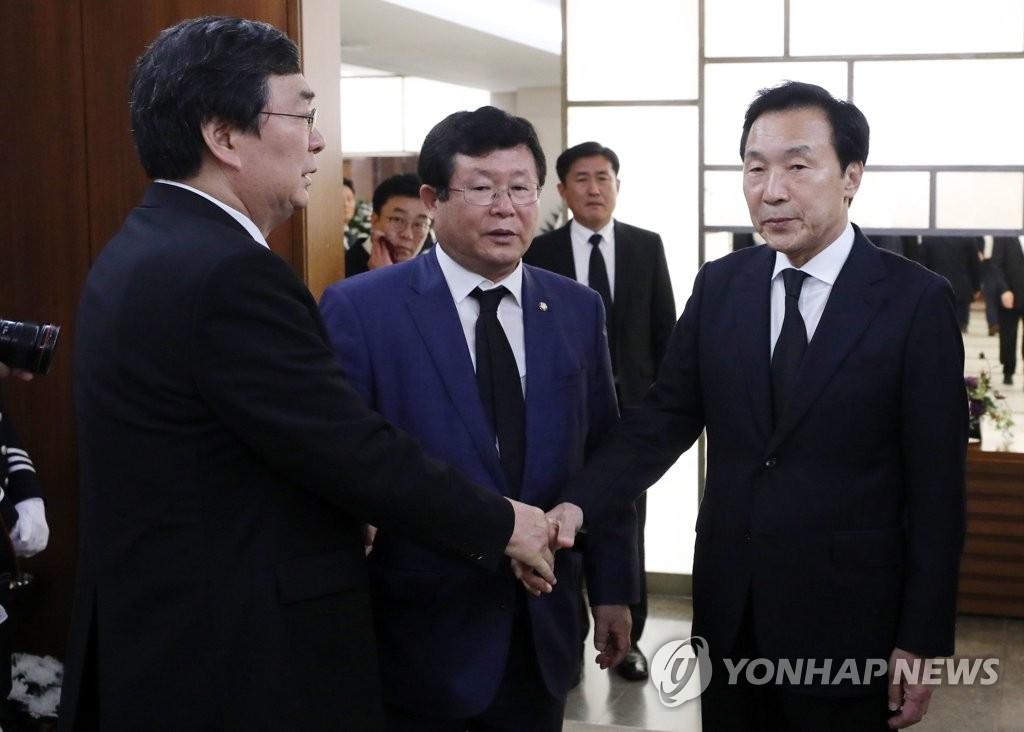 孙鹤圭(右)同李姬镐遗属握手致哀。 韩联社