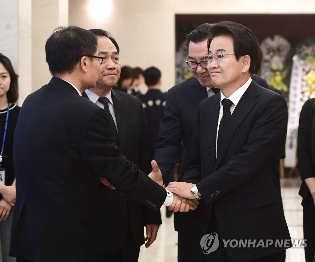 郑东泳(右)同李姬镐遗属握手致哀。 韩联社