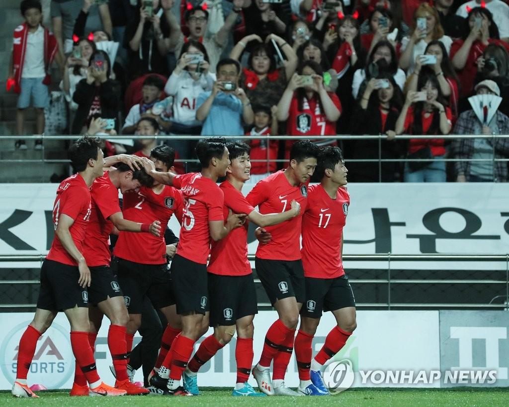 资料图片:6月11日,在首尔世界杯体育场,韩国男足在同伊朗队进行的热身赛上先入一球后相互庆祝。 韩联社