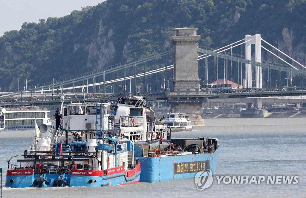 """资料图片:当地时间6月11日,在布达佩斯多瑙河,""""美人鱼""""号游船被驳船运往切佩尔岛。 韩联社"""