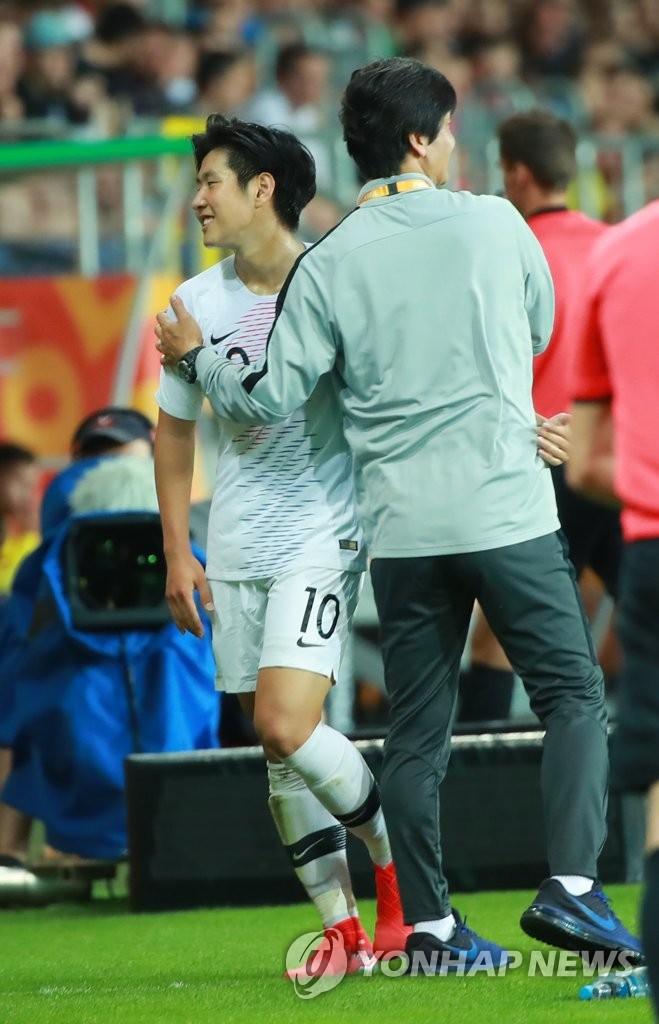韩国队主帅郑正溶(右)拥抱球员李康仁(左)以示鼓励。 韩联社