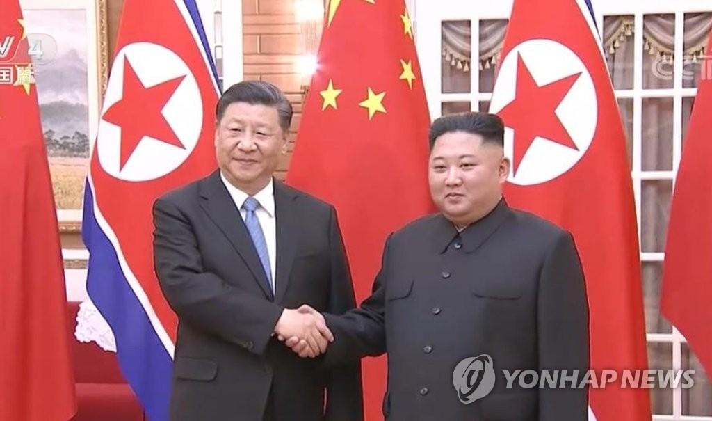 资料图片:6月20日,在平壤,习近平(左)与金正恩在会谈前握手合影。 韩联社/中国央视截图(图片严禁转载复制)