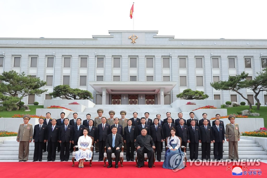 6月20日,在朝鲜劳动党中央总部,朝中两国首脑夫妇和党中央政治局委员们合影留念。 韩联社/朝中社(图片仅限韩国国内使用,严禁转载复制)