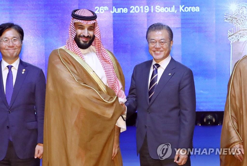 资料图片:6月26日,韩国总统文在寅(右)会见沙特阿拉伯王国王储兼副首相穆罕默德·本·萨勒曼。 韩联社