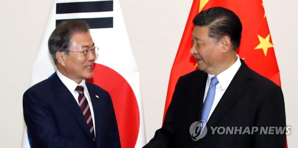6月27日,在日本大阪威斯汀酒店,韩国总统文在寅(左)同中国国家主席习近平合影。 韩联社