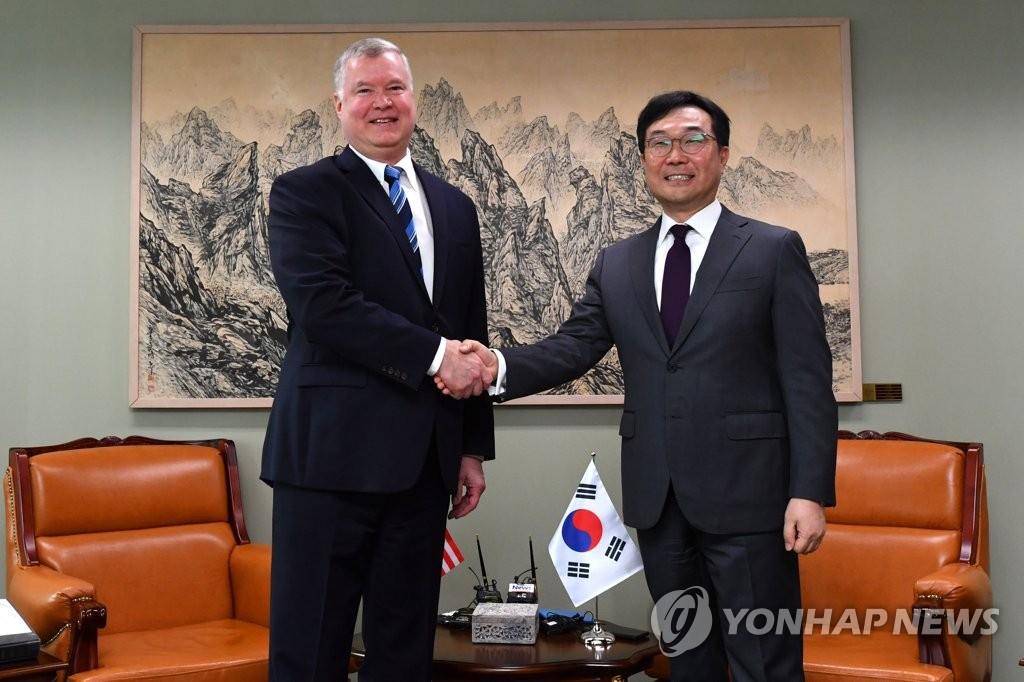 资料图片:6月28日,在首尔外交部大楼,韩国外交部和平交涉本部长李度勋(右)与到访的美国国务院对朝政策特别代表比根握手合影。 韩联社