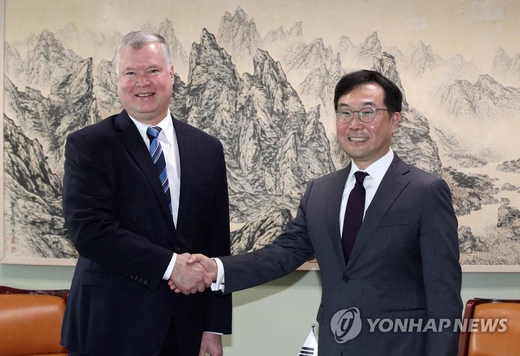 资料图片:6月28日上午,在首尔,李度勋(右)会见比根。 韩联社