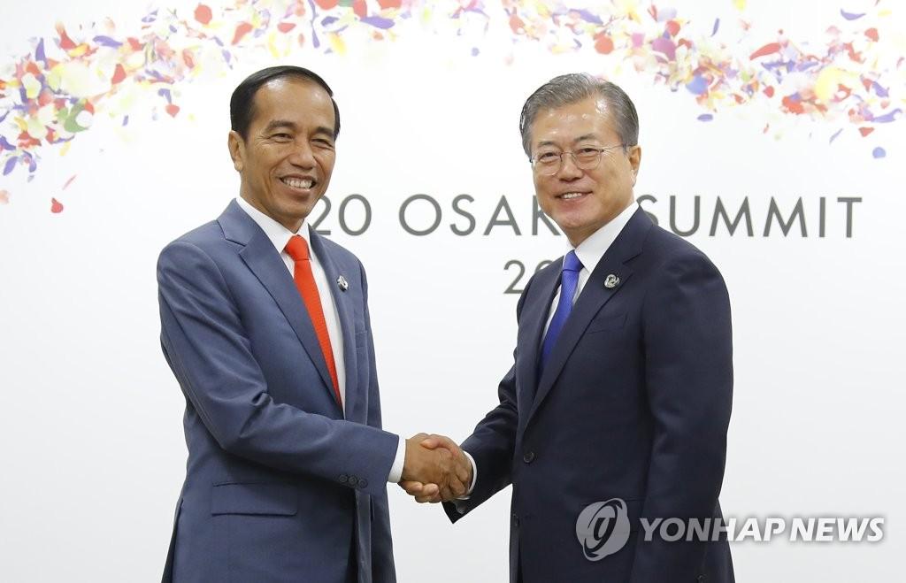 6月28日下午,在大阪会展中心,文在寅(右)和佐科在举行会谈前握手。 韩联社