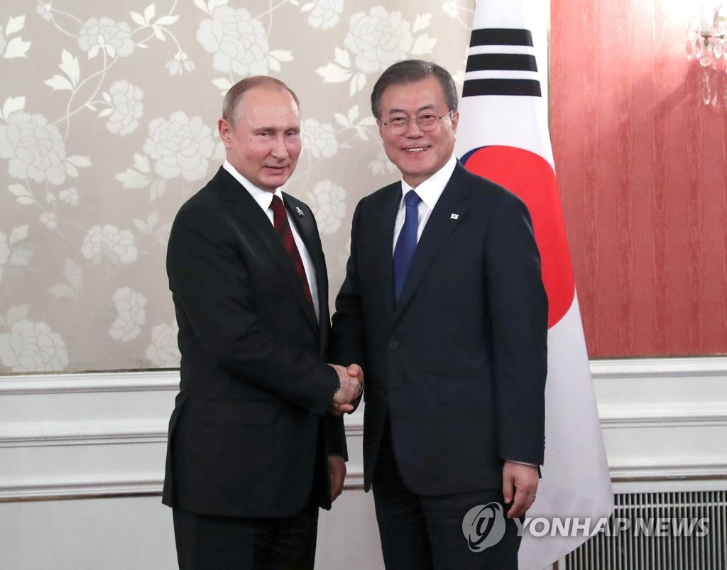 资料图片:2019年6月29日,在日本大阪,韩国总统文在寅(右)同俄罗斯总统普京在双边会谈开始前握手合影。文在寅为出席二十国集团领导人第十四次峰会访问大阪。 韩联社