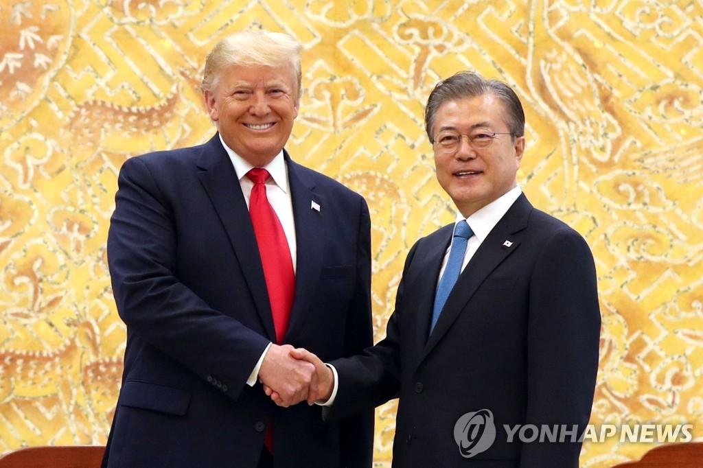 6月30日,在青瓦台,韩国总统文在寅(右)与美国总统特朗普握手合影。 韩联社