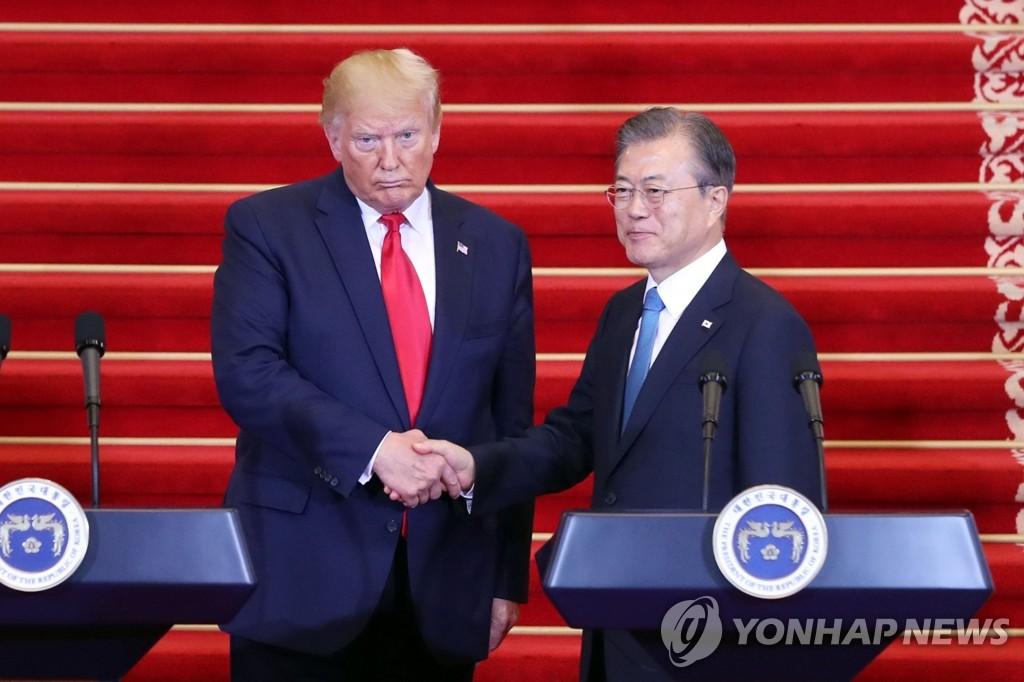 资料图片:6月30日,在青瓦台,韩国总统文在寅(右)与美国总统特朗普在记者会后握手。 韩联社