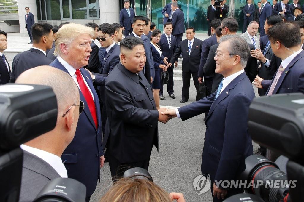 6月30日,在韩朝边境板门店韩方一侧的自由之家前,文在寅(右)与金正恩握手。 韩联社