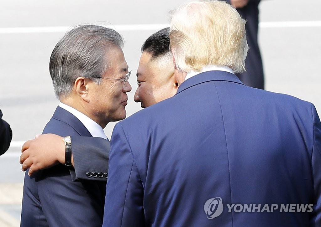 6月30日下午,在板门店,文在寅(左)在特朗普(右)面前拥抱送别金正恩。 韩联社