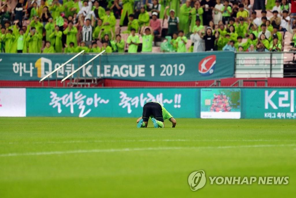 资料图片:7月7日,在全北现代和城南FC比赛中,金信煜进球后跪拜粉丝。 韩联社