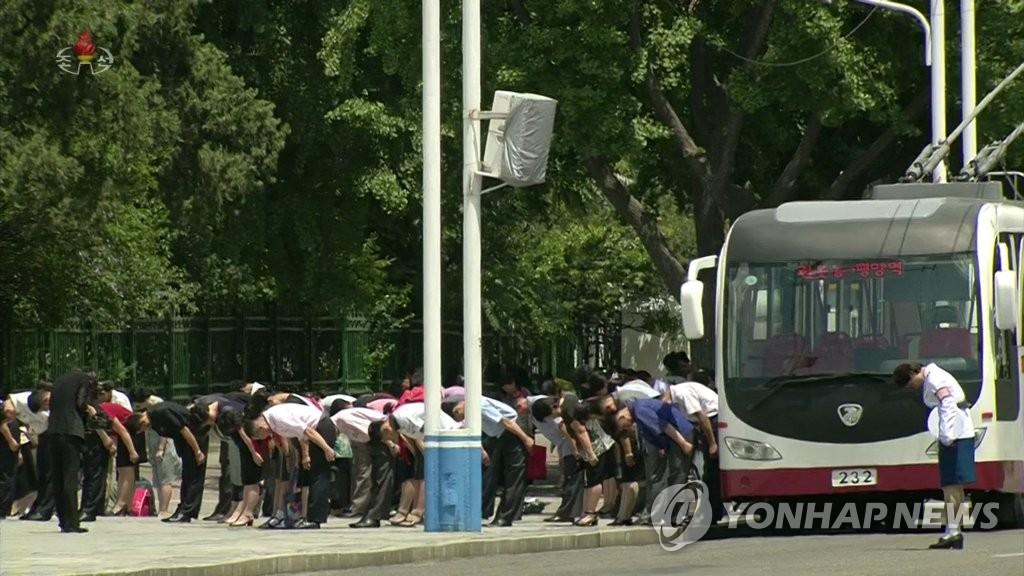 7月8月中午12点,平壤一辆公交车的司乘人员和乘客们下车鞠躬默哀,缅怀金日成。 韩联社/朝鲜央视(图片仅限韩国国内使用,严禁转载复制)