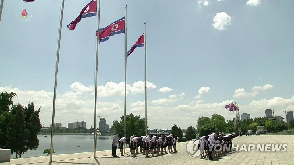 7月8日中午12点,平壤群众在半旗下缅怀金日成。 韩联社/朝鲜央视(图片仅限韩国国内使用,严禁转载复制)