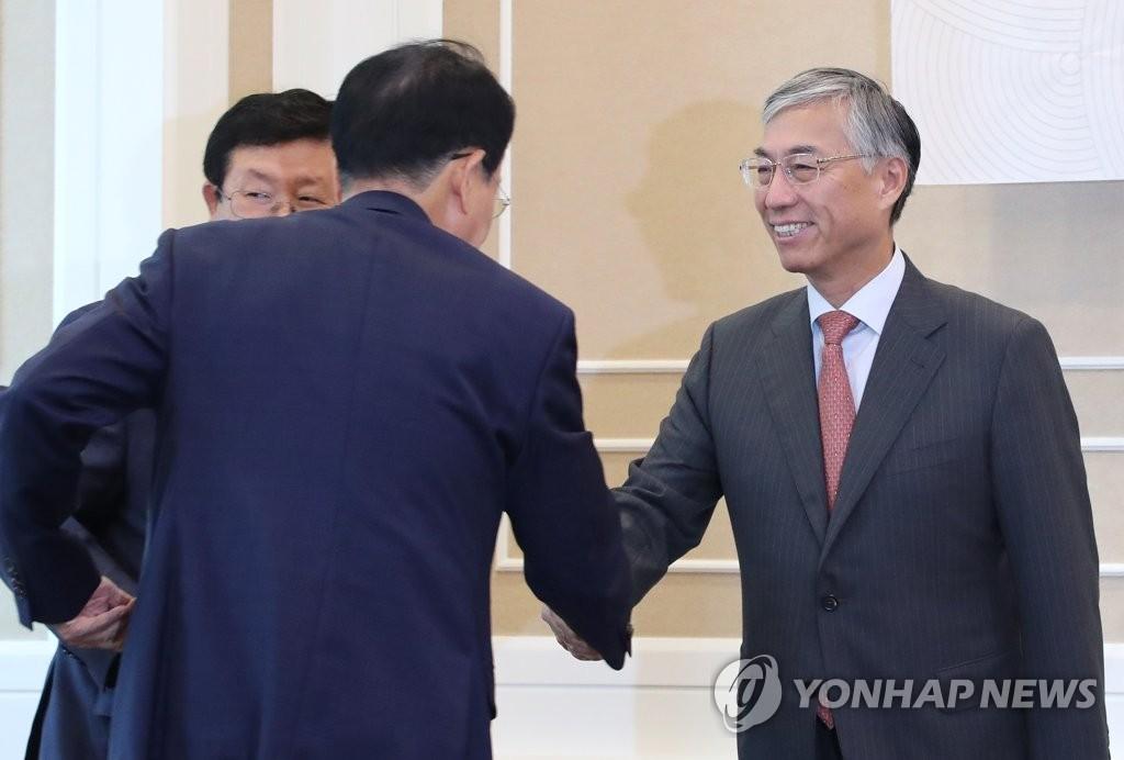 7月10日上午,在韩国国会,中国驻韩大使邱国洪(右)与韩国议员握手。 韩联社