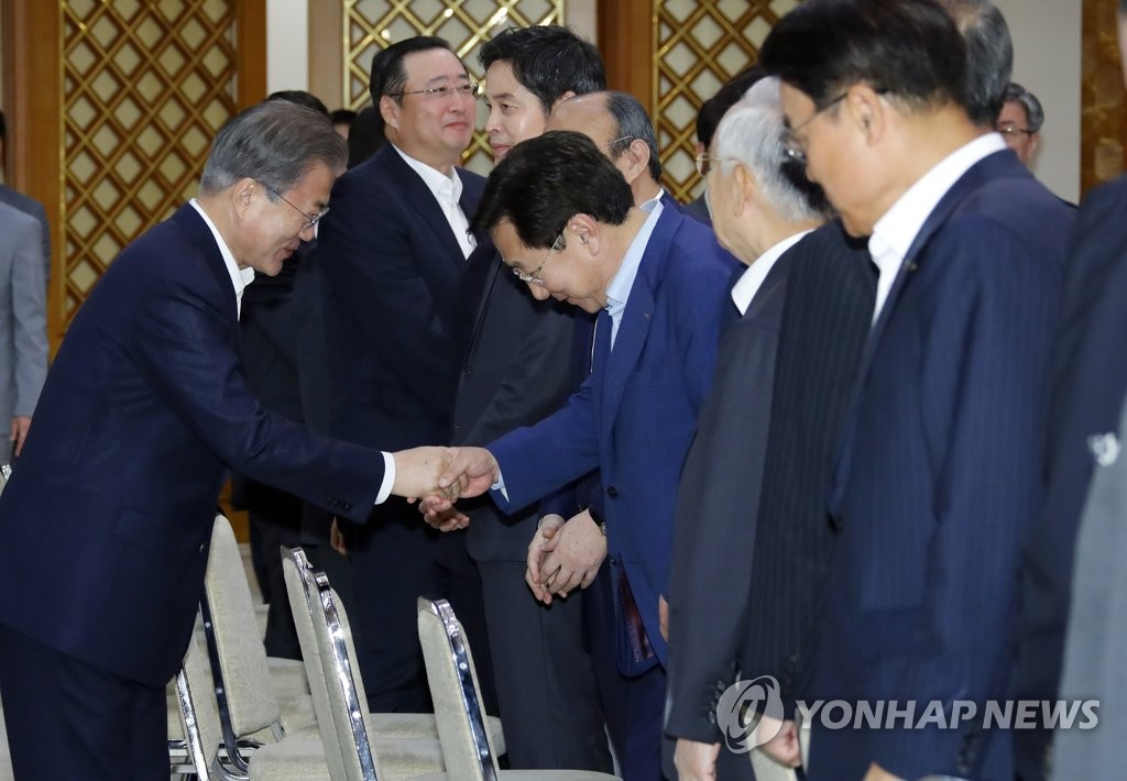 10月4日,在青瓦台,文在寅(左)和金基文握手。 韩联社