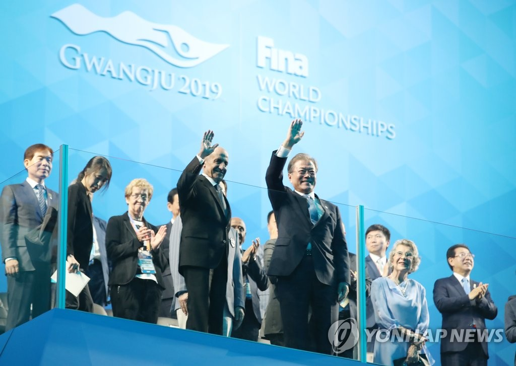 7月12日下午,文在寅(前排右)出席2019光州世游赛开幕式并向现场人员挥手致意。 韩联社