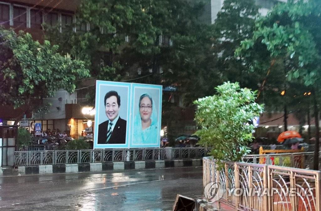 资料图片:当地时间7月13日,在孟加拉国达卡,李洛渊(左)和哈西娜的大型照片悬挂在市区。 韩联社