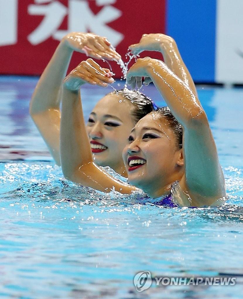 7月16日,2019世界游泳锦标赛艺术游泳双人自由自选预赛在光州念珠综合体育馆举行。图为韩国选手白瑞妍和具艺模在水中展现优美姿态。 韩联社