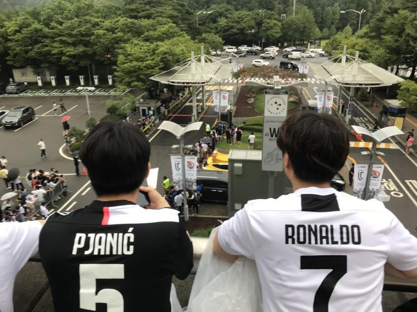 资料图片:7月26日下午,在首尔世界杯体育场,韩国球迷等待尤文图斯队头号球星C罗亮相。球迷们排起长龙,等待观赛一睹C罗绿茵风采。 韩联社