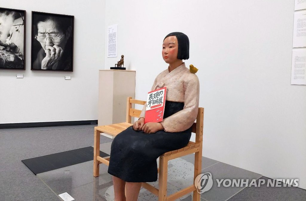 """资料图片:8月4日,在名古屋市爱知文化艺术中心8层,和平少女像的手上放着""""表达的不自由展""""宣传册。 韩联社"""