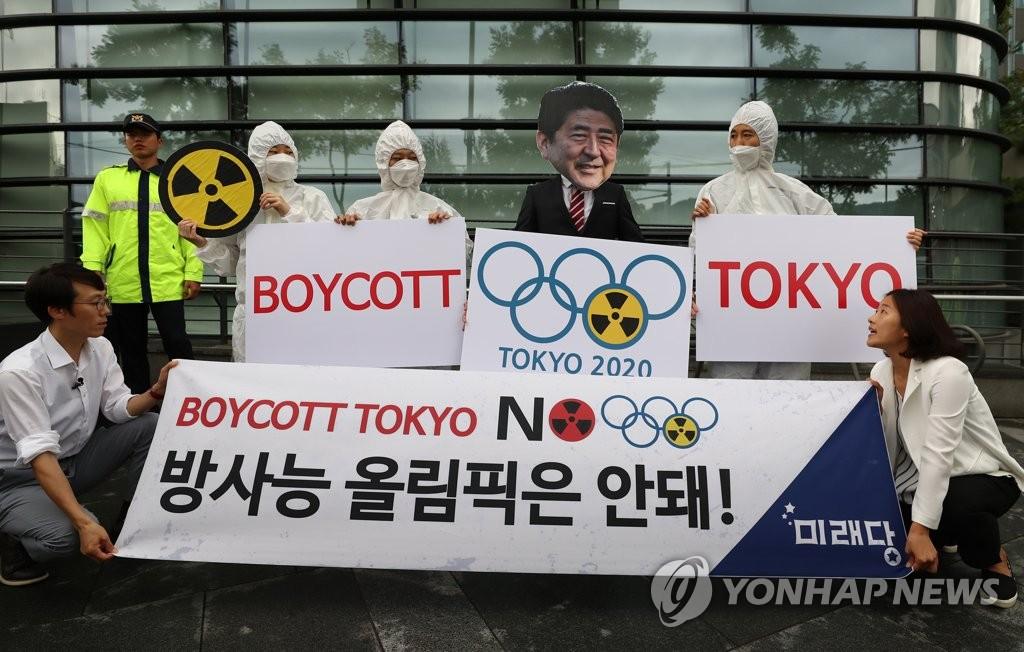 资料图片:8月7日上午,在日本驻韩使馆门前,韩国未来党党员们举行记者会手持标语呼吁抵制安倍政府的核泄漏奥运会。 韩联社