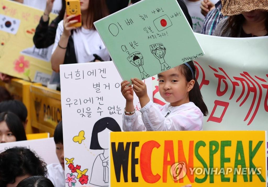 资料图片:8月7日,在首尔市原日本驻韩使馆前,解决日军性奴制问题的第1399次周三集会人员手举各种标语敦促日本政府道歉。 韩联社