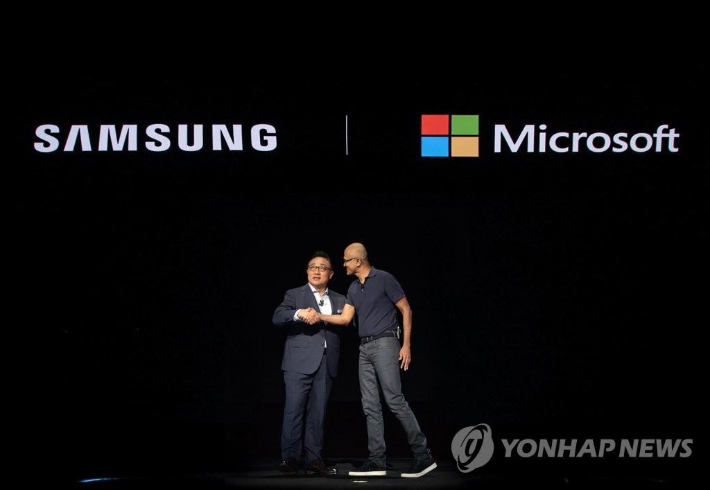 资料图片:当地时间8月7日,在美国纽约举行的Galaxy Note10发布会上,三星电子总裁高东真(左)与首席执行官(CEO)纳德拉亲切握手。 韩联社/三星电子供图(图片严禁转载复制)