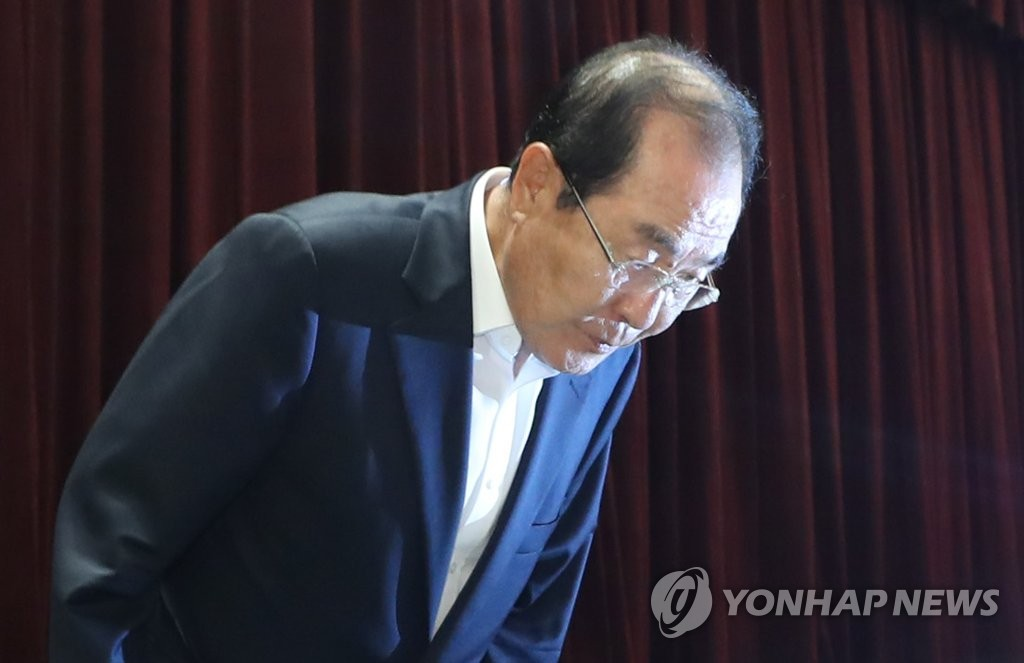 8月11日,尹东汉在记者会上低头道歉。 韩联社