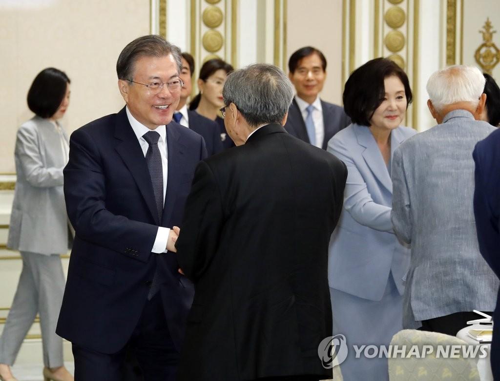 8月13日,在青瓦台迎宾馆举行的抗日功臣及后人午餐会上,韩国总统文在寅(左)和与会者握手。 韩联社