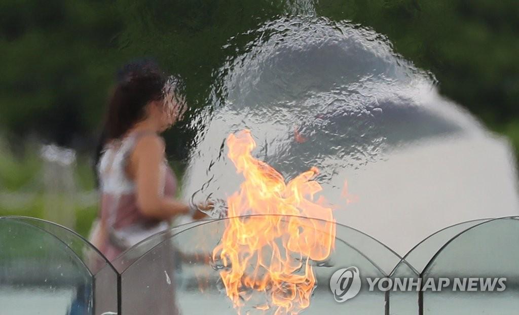 资料图片:2019年8月13日,在首尔奥林匹克公园,一名市民路过和平门下燃烧的圣火。当天,韩国大部分地区的最高气温均升至33摄氏度以上。 韩联社