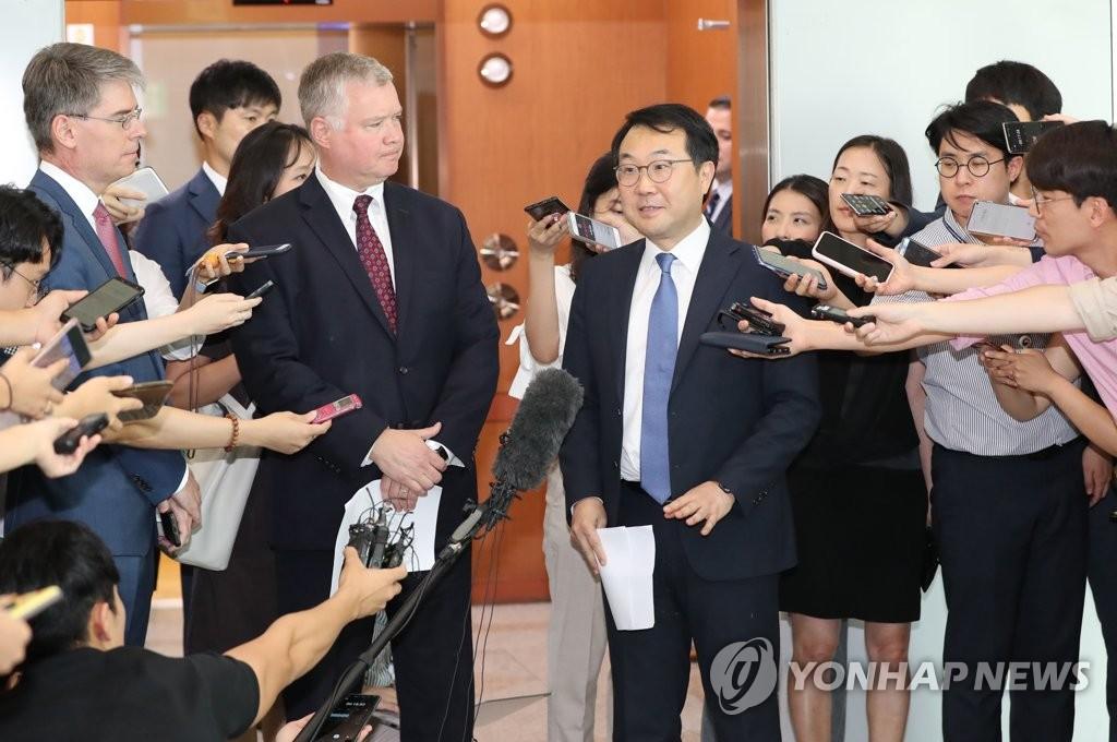 资料图片:8月21日,在首尔,比根(左)和李度勋结束会谈后接受记者采访。 韩联社
