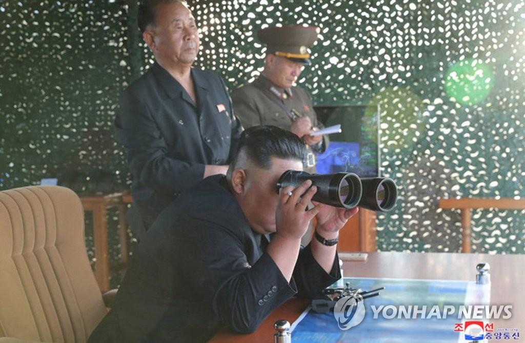 8月24日,金正恩通过望远镜观看超大型火箭炮的试射结果。 韩联社/朝中社(图片仅限韩国国内使用,严禁转载复制)